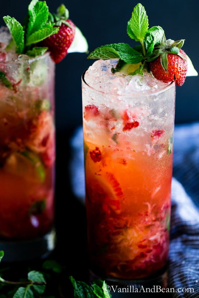 Strawberry Mojitos in a glass garnished with strawberries and mint.
