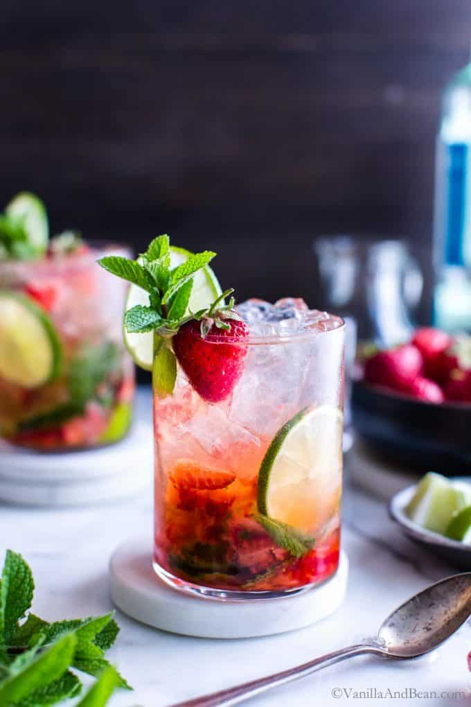Two Strawberry mojitos in a glass garnished with mint, lime and a strawberry ready for sharing.