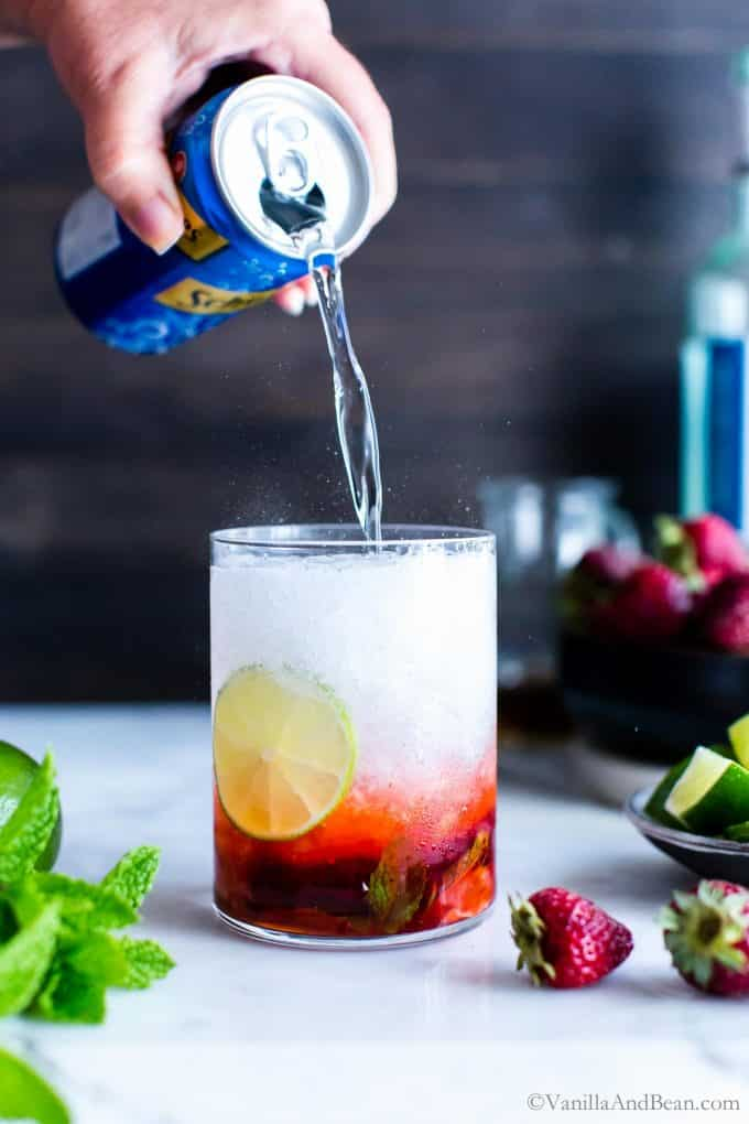 Club soda being poured into a strawberry mojito with ice .
