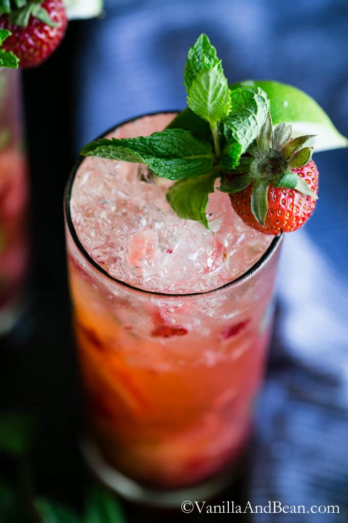Strawberry Mojito in a highball glass garnished with strawberry and mint leaves.