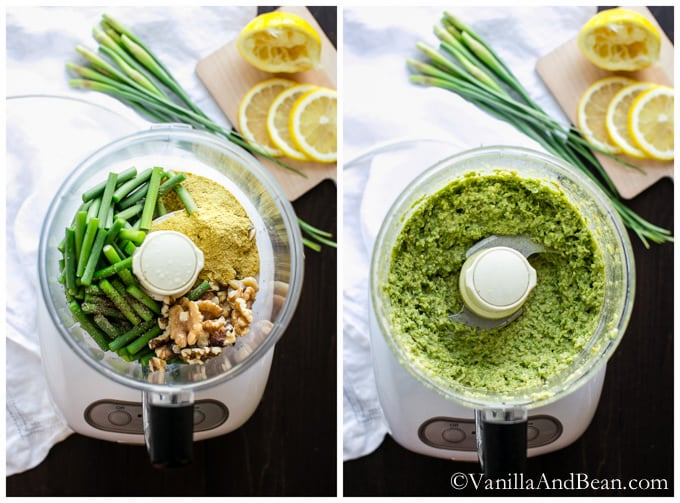 Ingredients for the Vegan Garlic Scape Pesto in a food processor surrounded by lemon slices and garlic scape.