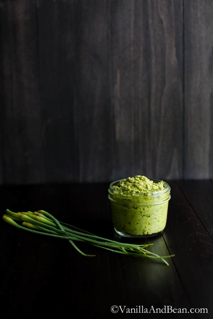 A small glass jar of Vegan Garlic Scape Pesto beside fresh garlic scape.