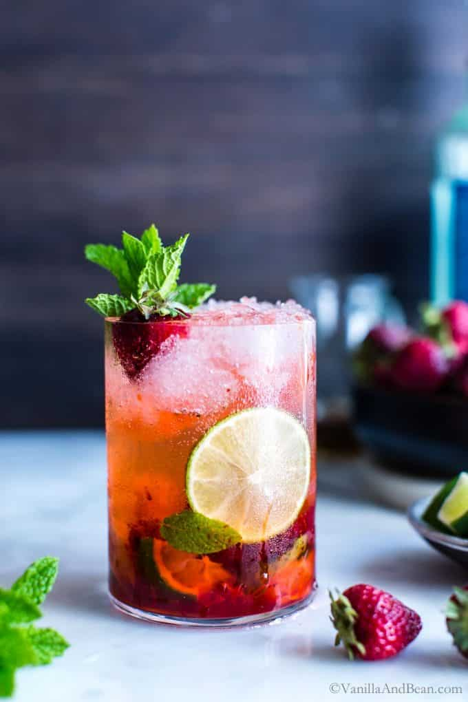 Strawberry mojito in a glass garnished with mint, lime and a strawberry.