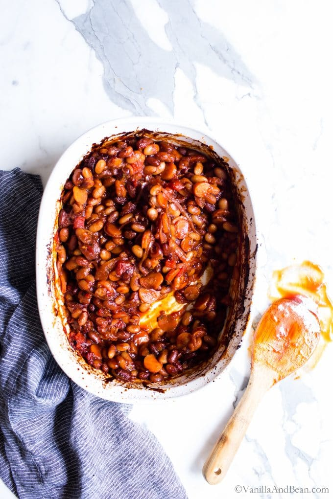 BBQ Baked Beans Vegetarian Recipe in a baker with a spoon with BBQ sauce on the side.