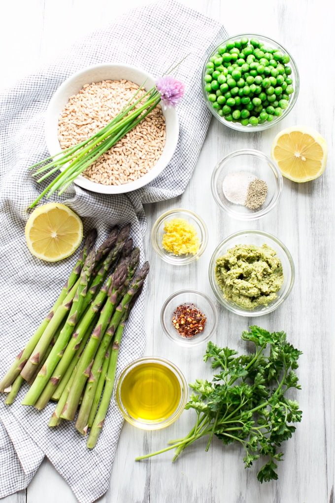 Ingredients for Creamy Farro with Pesto Asparagus and Peas on a table.