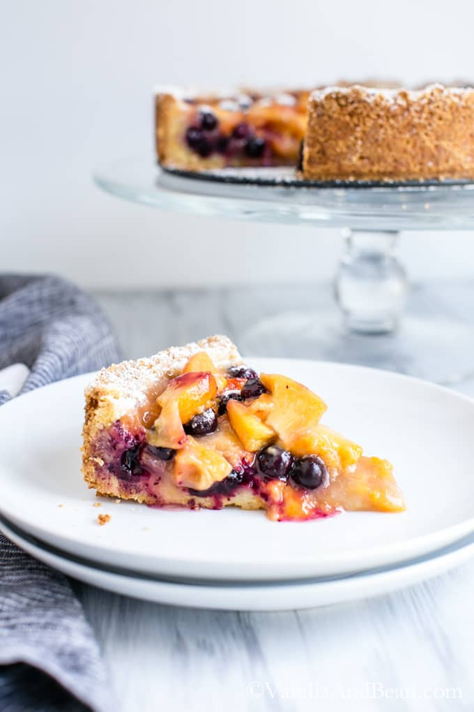 A slice of Blueberry Peach Cobbler-Tart on a small plate with the rest of the pie on a cake stand in the background.