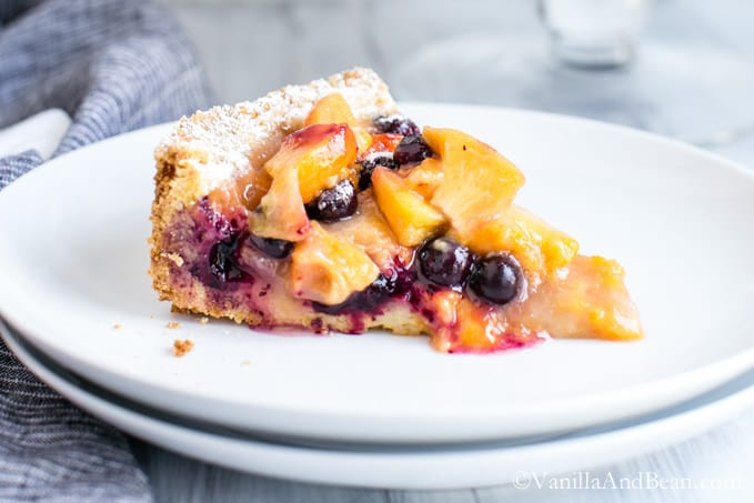A slice of Blueberry Peach Cobbler-Tart on a small plate.