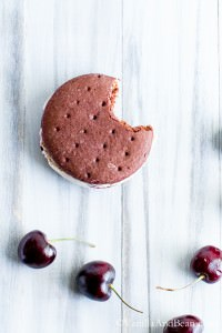 Chocolate Ice Cream Sandwich Cookie with a bite and fresh cherries below it.