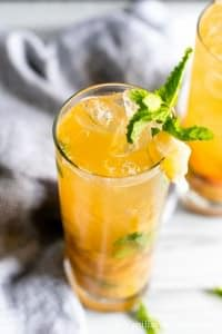 A tall glass of Bourbon Peach Smash with ice decorated with mint and candied ginger.