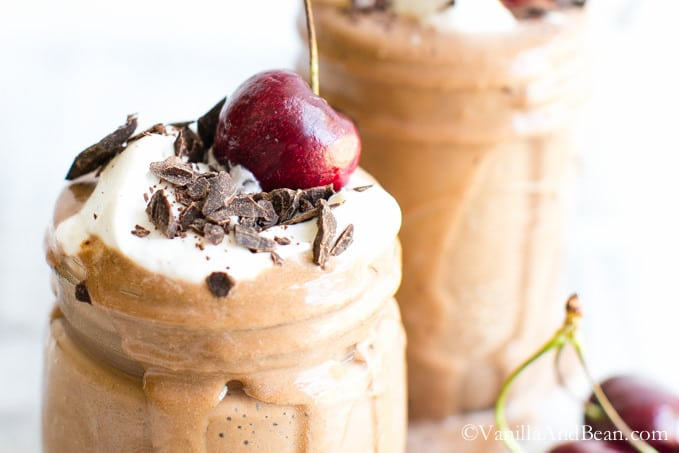Mocha Shake in two glasses topped with cherries and chopped chocolate.