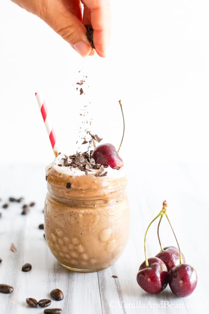 Sprinkling a glass of mocha shake with chopped chocolate. Fresh cherries beside the glass.