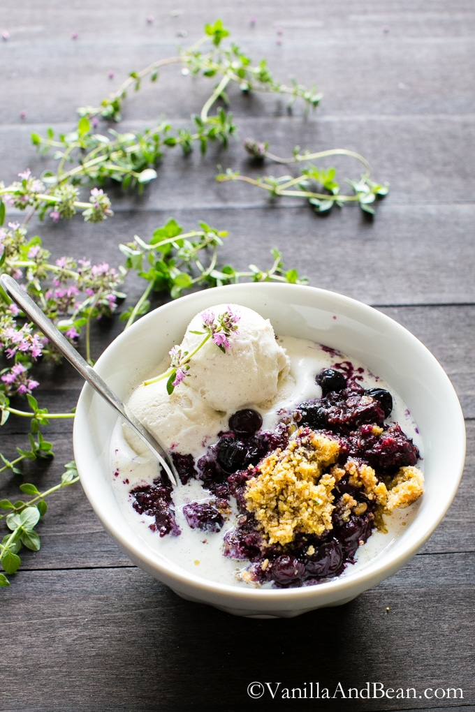 Blueberry Lemon-Thyme Cornmeal Crisp in a bowl with ice cream and spoon.