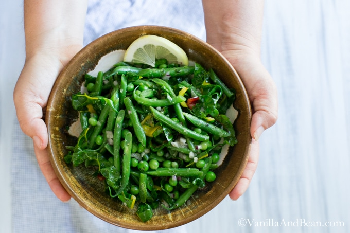 A hand howling a bowl of Green Bean Salad with Peas, Chard and Dijon Tarragon Vinaigrette.