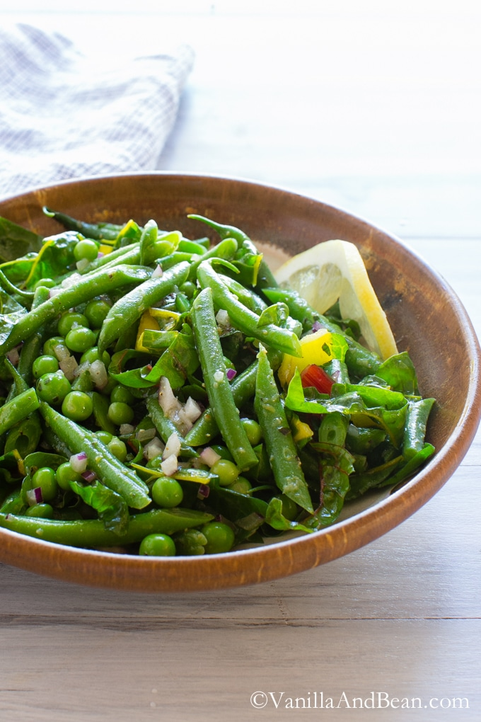 A bowl of Green Bean Salad with Peas, Chard and Dijon Tarragon Vinaigrette.