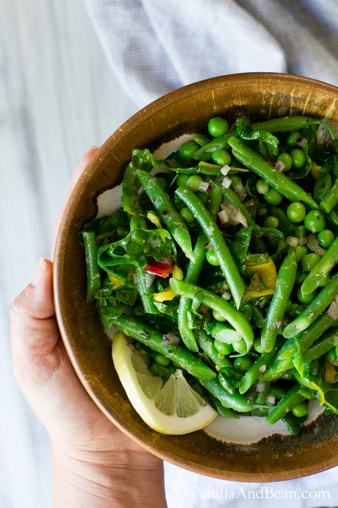 A hand holding a bowl of Green Bean Salad with Peas, Chard and Dijon Tarragon Vinaigrette.