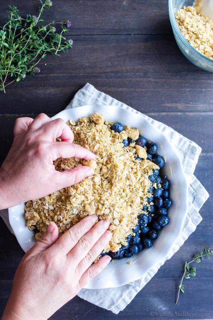 Hands spreading the crumble on top of a Blueberry Cornmeal Crisp.