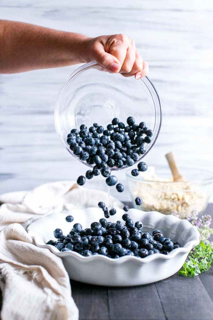Blueberries being poured into a deep dish pie plate getting ready to bake a blueberry crisp.