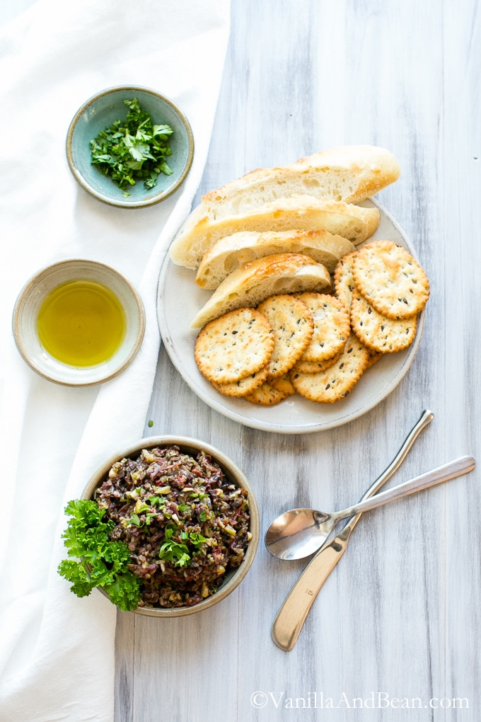 Overhead shot of olive tapenade recipe shared with olive oil, crackers and bread.