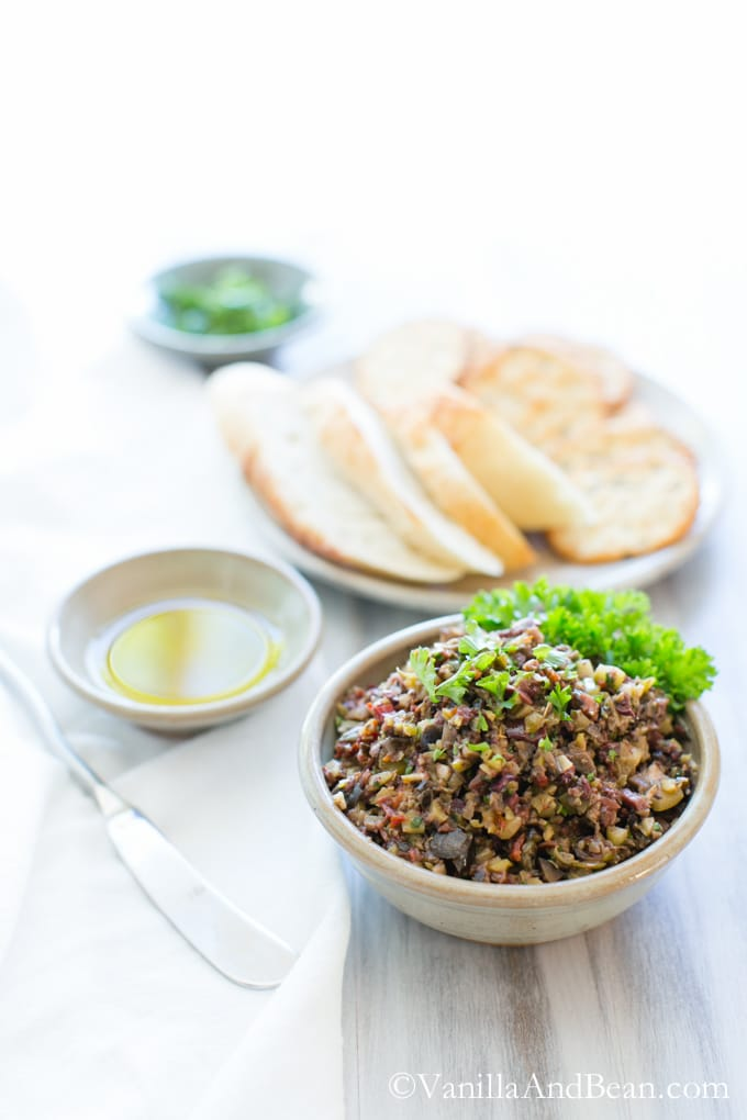 Vegan Olive Tapenade in a bowl shared with bread and crackers.