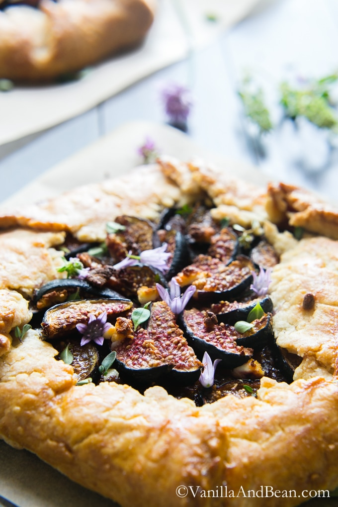 Caramelized Onion and Fig Galette with Goat Cheese and Herbs on a wood board ready for sharing.
