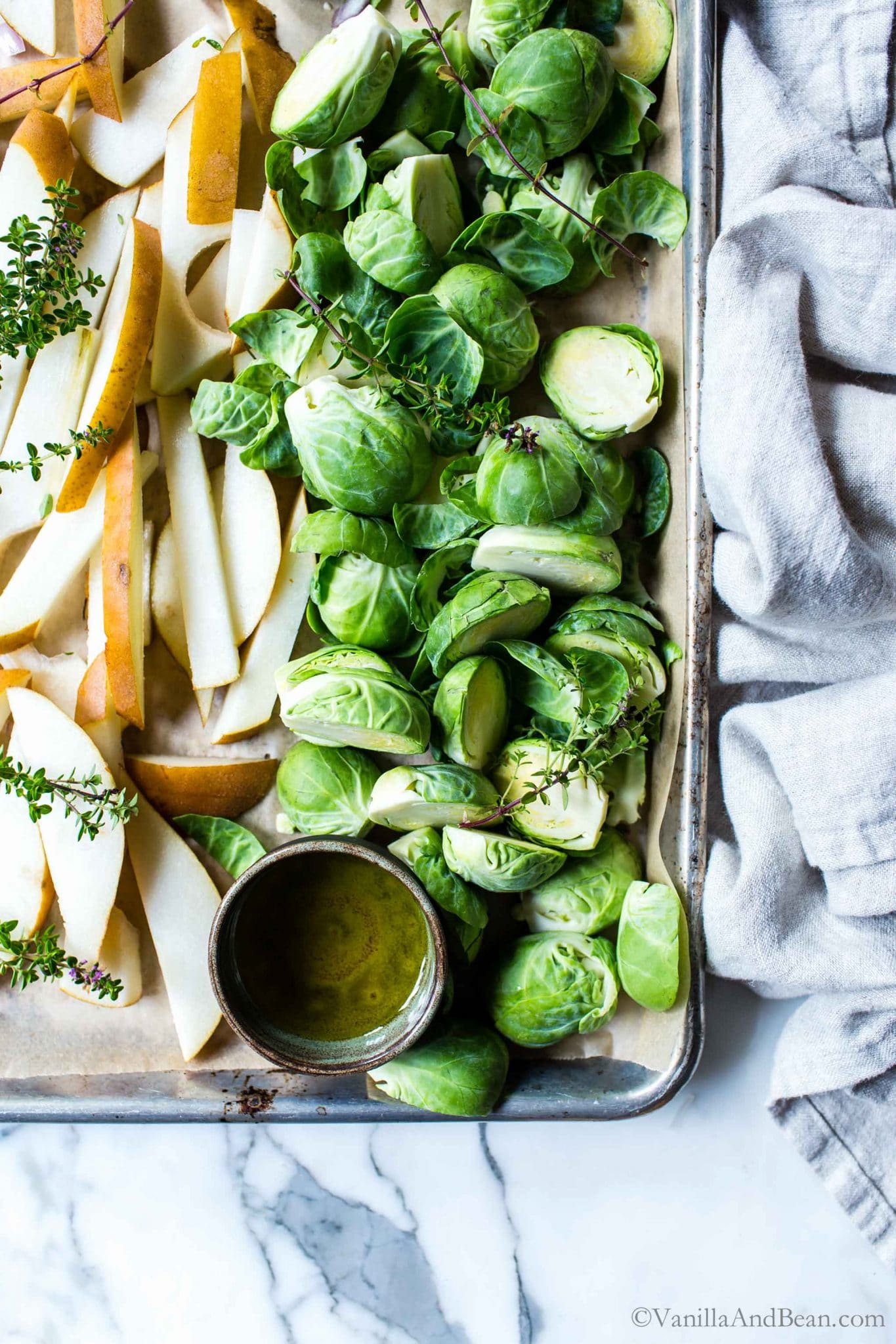 Sliced Brussels sprouts with pears and Thyme ready for roasting on a sheet pan.