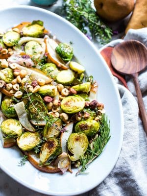 Oven roasted brussels sprouts with pear and thyme on a serving platter.