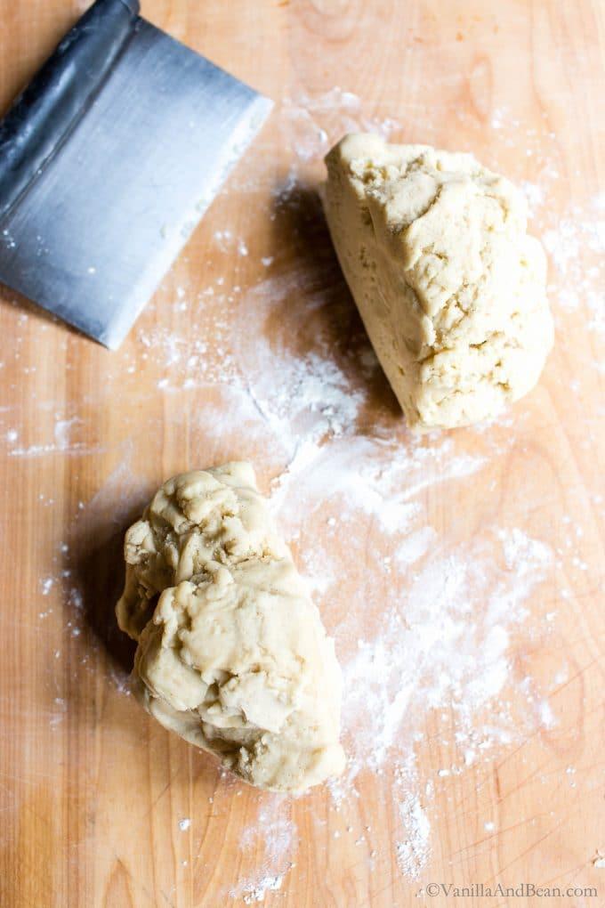 Dividing shortbread cookie dough on a floured board.