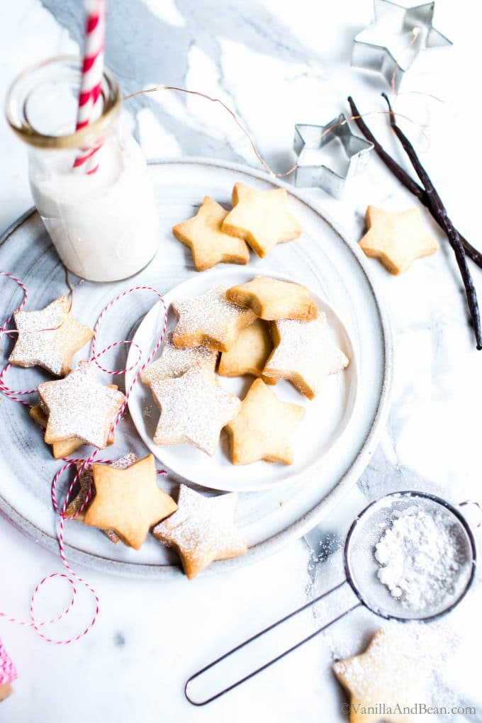 Vanilla Bean Cutout Cookies on a plate with a glass of milk.