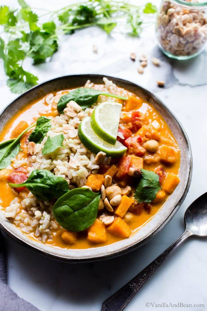 West African Peanut Stew in a bowl topped with lime, spinach, cilantro and rice, ready to eat.