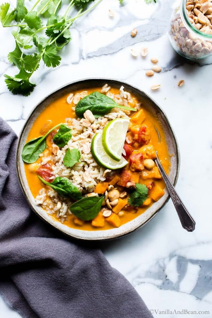 Sweet Potato and Peanut Soup in a bowl topped with limes and cilantro.