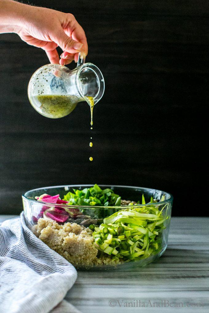 Pouring dressing over the asparagus quinoa salad.
