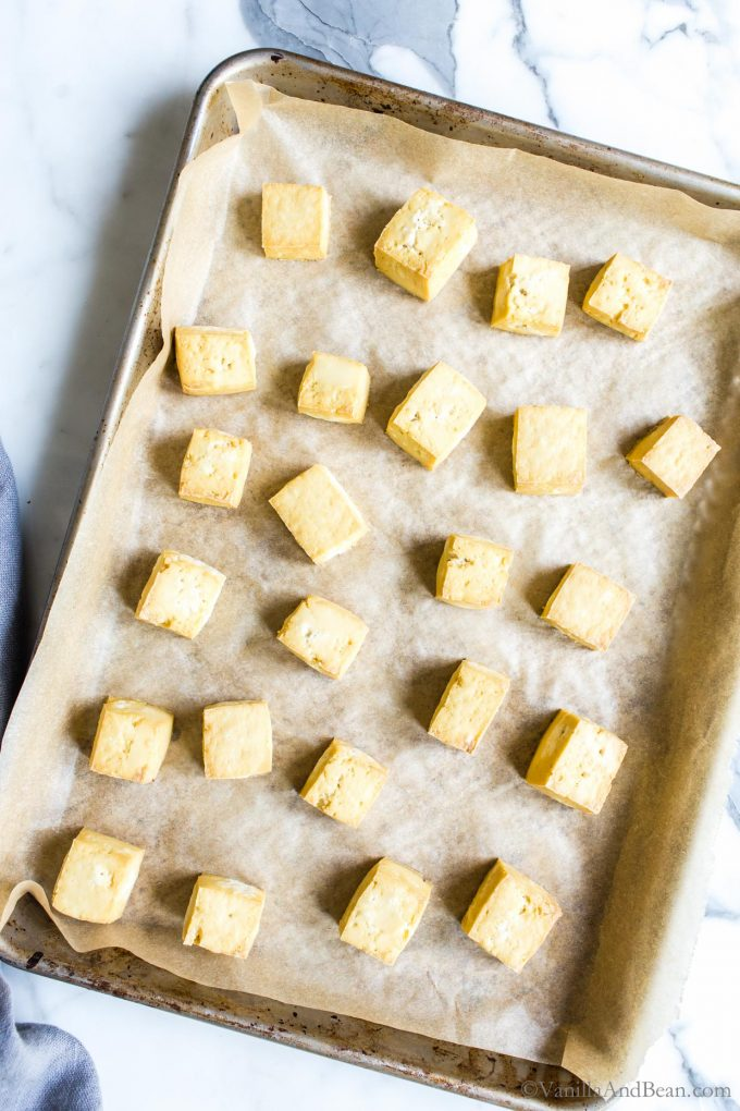 Diced tofu on a parchment lined sheet pan after baking.