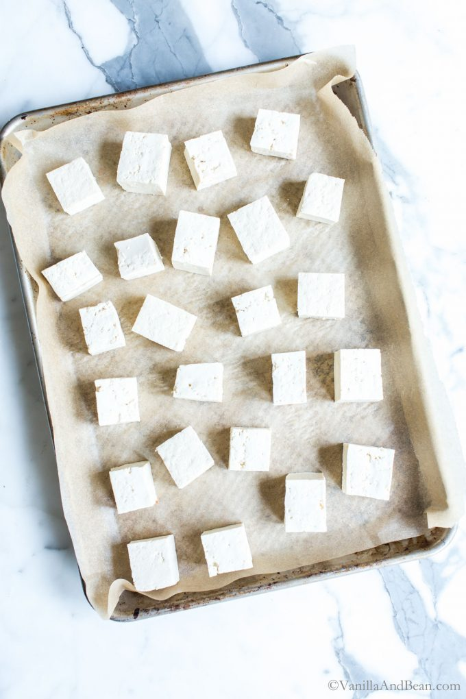 Diced tofu on a parchment lined sheet pan ready for baking.