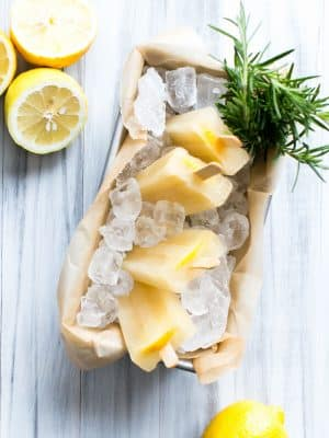 Rosemary Lemon Popsicles arranged in a pan filled with ice and rosemary.