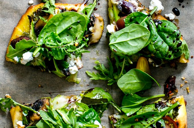 Flatbread Pizza Salad with Pesto, Shaved Asparagus, Mushrooms and Feta cut into four wedges.