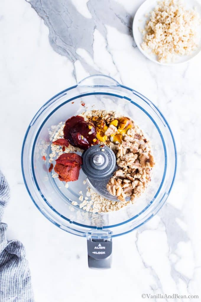 Walnuts, spices and oats in a food processor bowl.