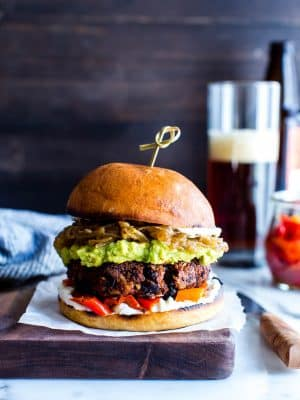 Best bean burgers on a board topped with saucy onions and guacamole.