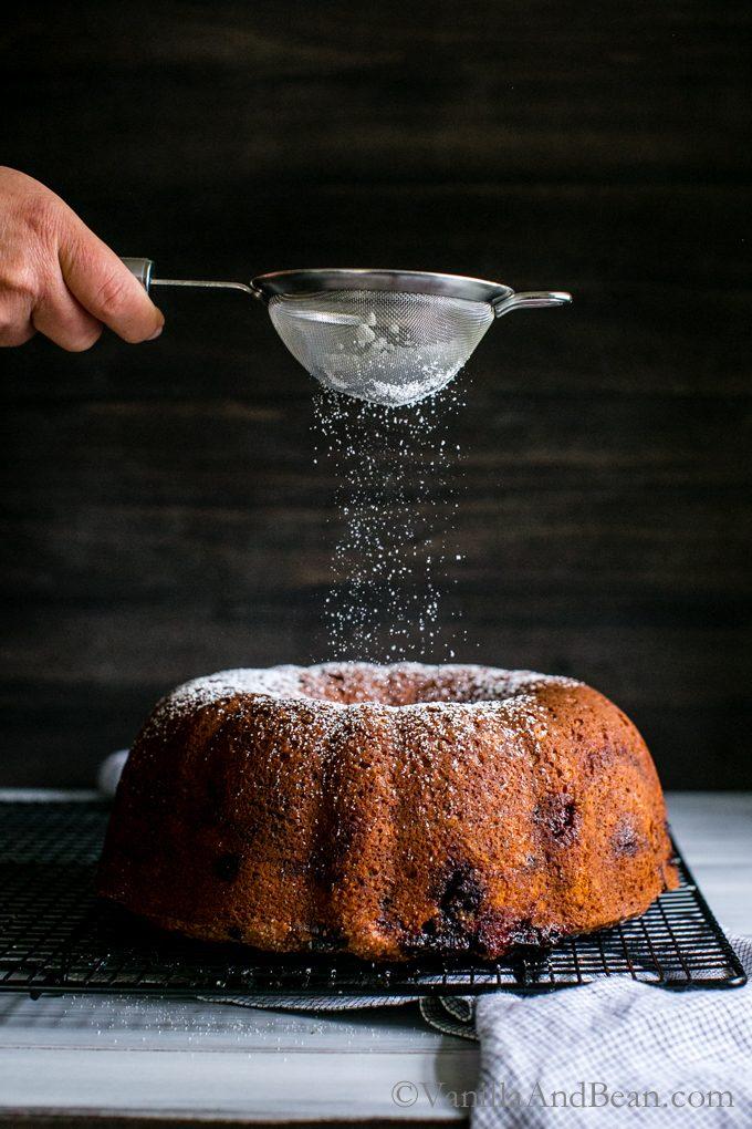 Sprinkling powder sugar on top of a Blueberry Cinnamon Yogurt Coffee Cake