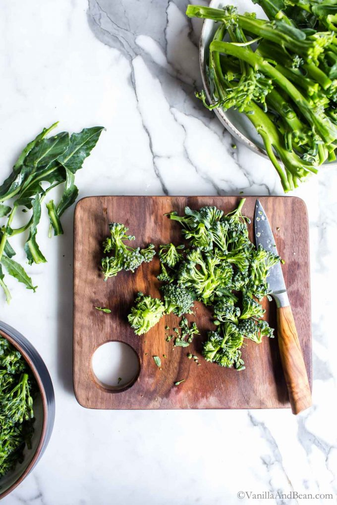 Trimmed Broccolini on a cutting board with knife.