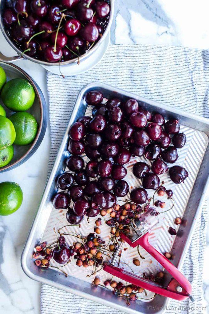Pitting bing cherries on a sheet pan.