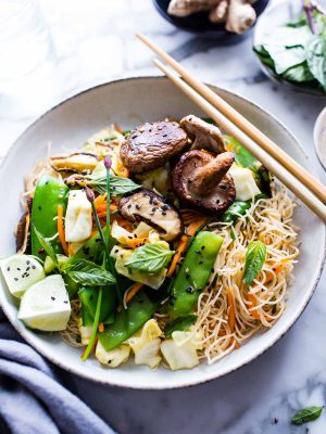 Vegan rice noodle recipe in a bowl garnished with onions and sesame seeds. Chopsticks rest on the side of the bowl.