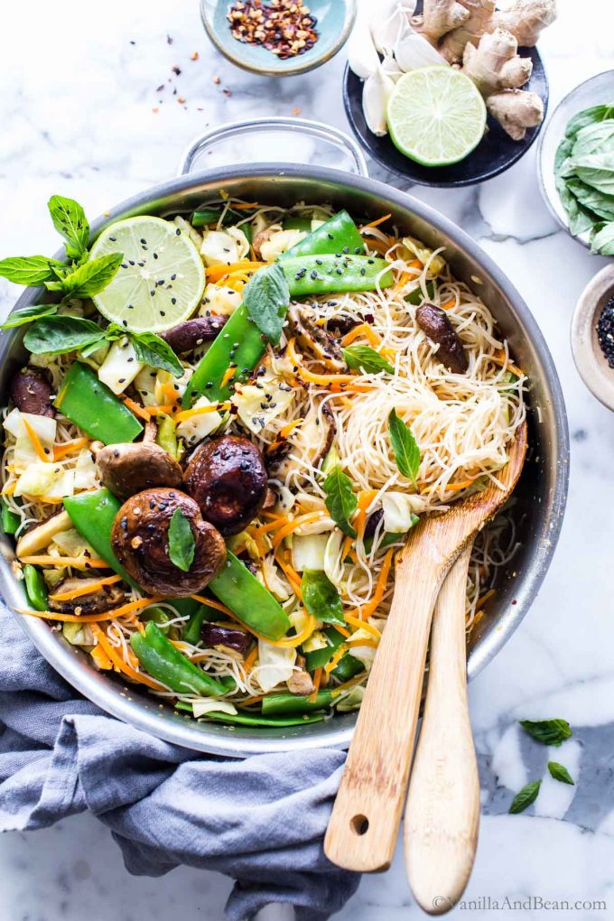 Vegetarian Rice Noodle recipe in a skillet garnished with lime, herbs and sesame seeds. Two spoons rest on the side.