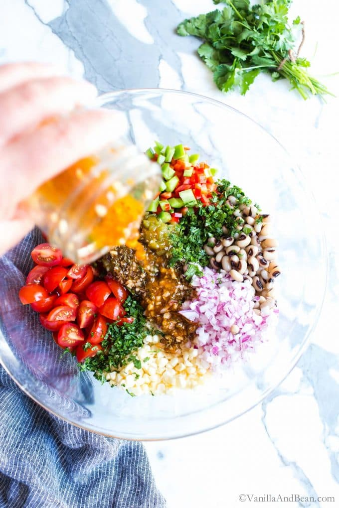 Black Eyed Pea Salad recipe in a bowl getting dressing poured over it.
