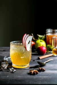 Bourbon Apple Cider Shrub Cocktail in a glass garnished with apple slices.