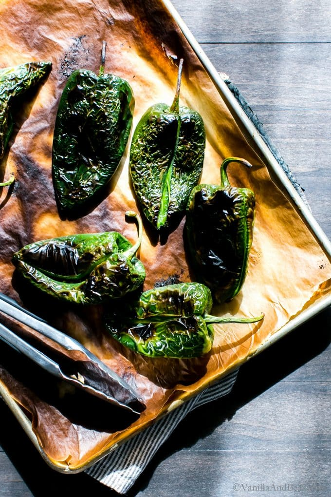Charred Poblano Peppers on a parchment lined sheet pan.
