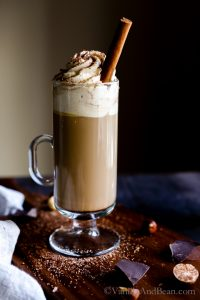 Boozy Coffee in a tall coffee glass topped with whipped cream and a cinnamon stick.