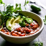 A cozy Kabocha Two Bean Chili simmered in a chipotle and poblano base with fire roasted tomatoes and warming spices in a bowl topped with avocado, onion and cilantro.