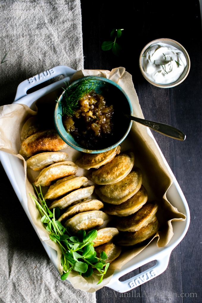Vegetarian or Vegan Pierogies in a serving dish served with caramelized onions and sourcream.