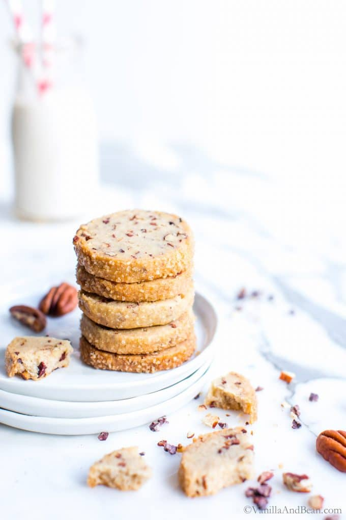 Pecan Shortbread Cookies stacked tall on a plate with milk in a glass.