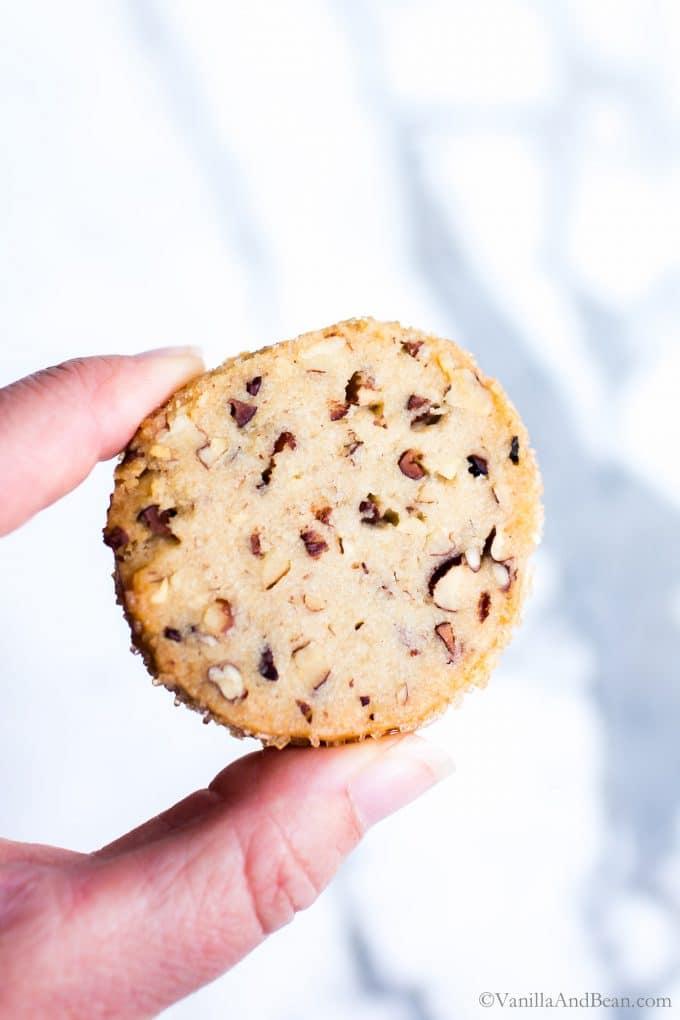 Pecan Shortbread Cookie held between two fingers.